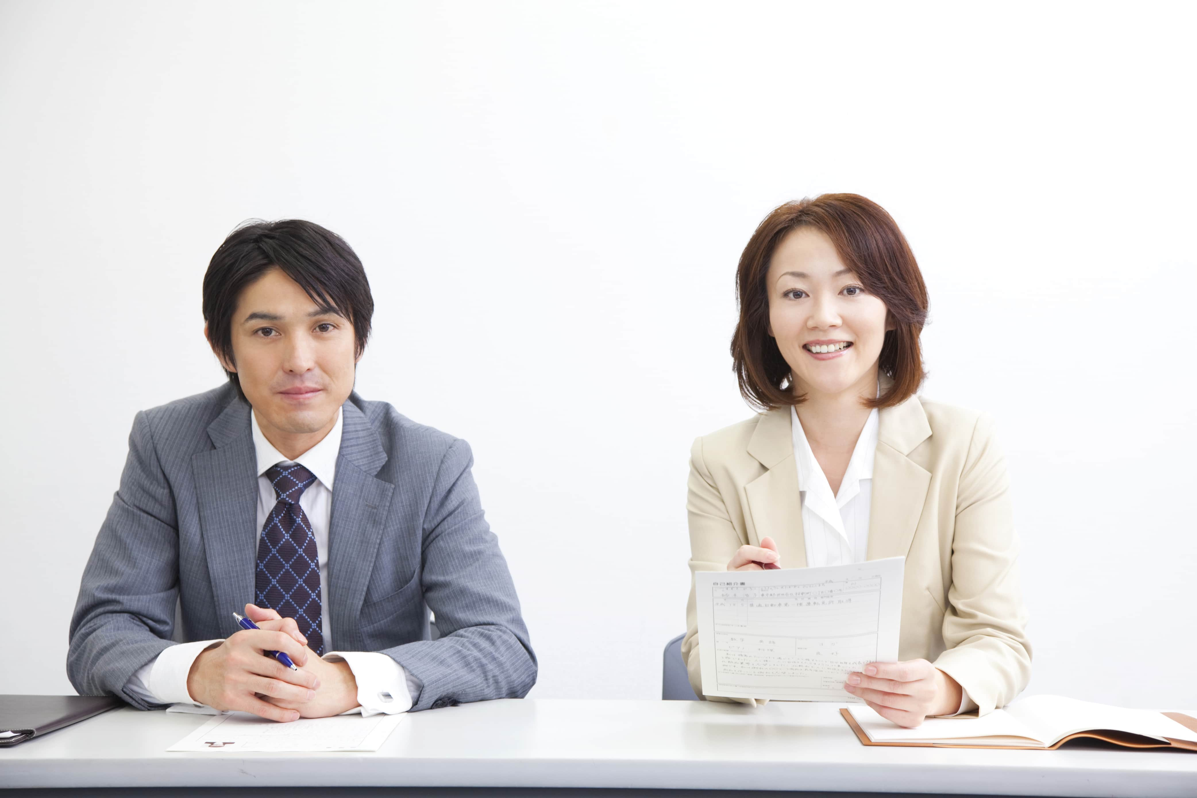 Male and female Japanese interviewers sitting behind a desk