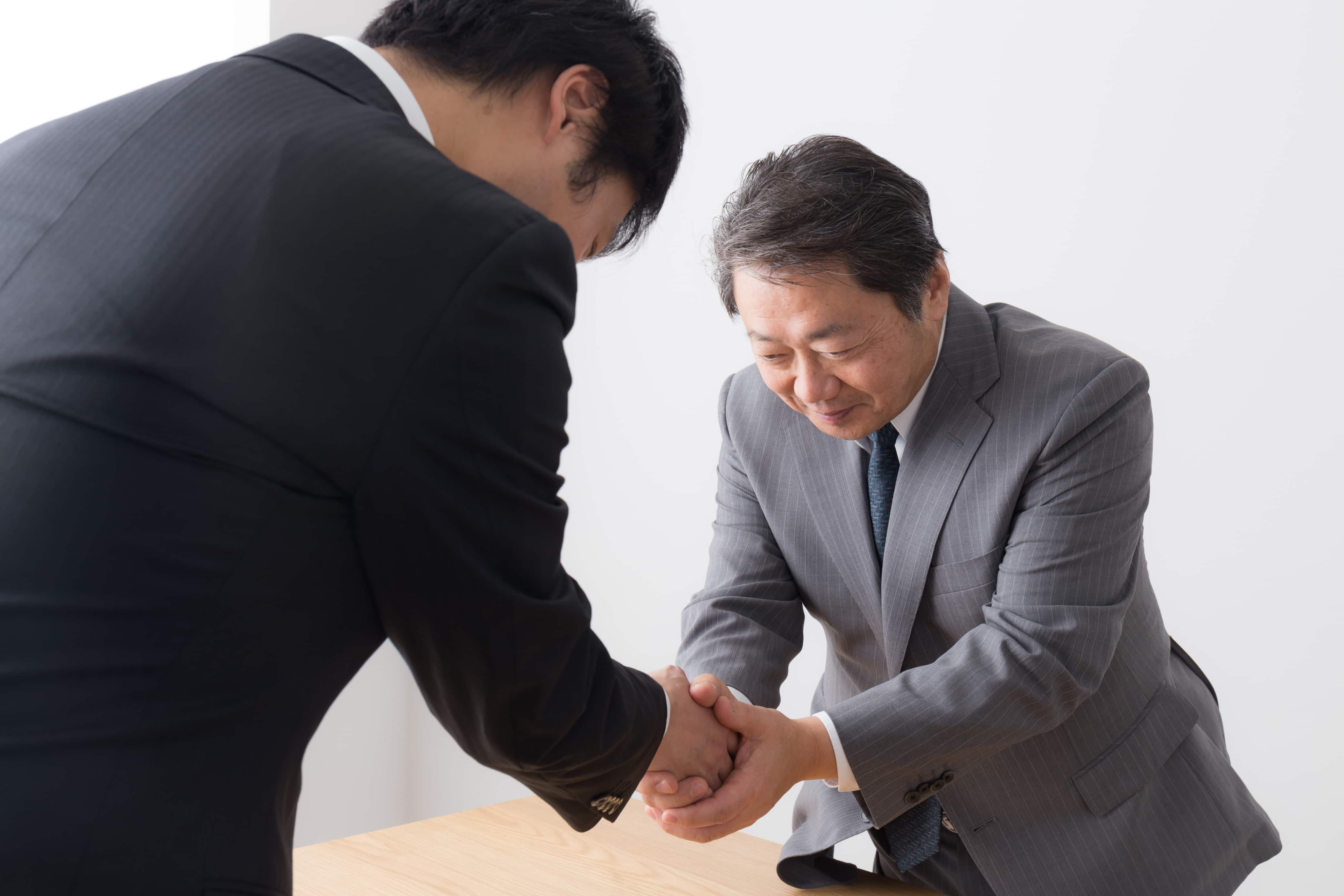 Two Japanese businessmen bowing and shaking hands