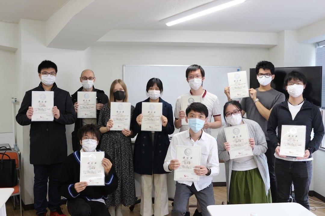 Akamonkai students holding up Japanese certificates