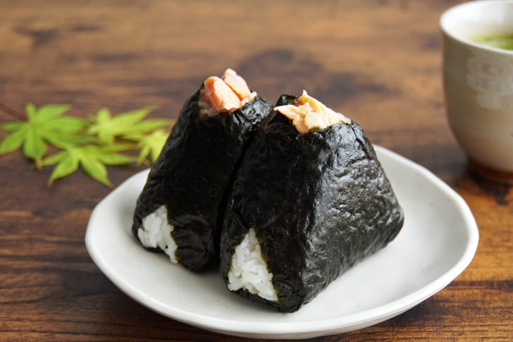 2 salmon onigiri on a plate on a wooden table